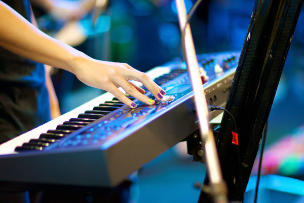 hand of musician playing keyboard in concert with shallow depth of field, focus on right hand