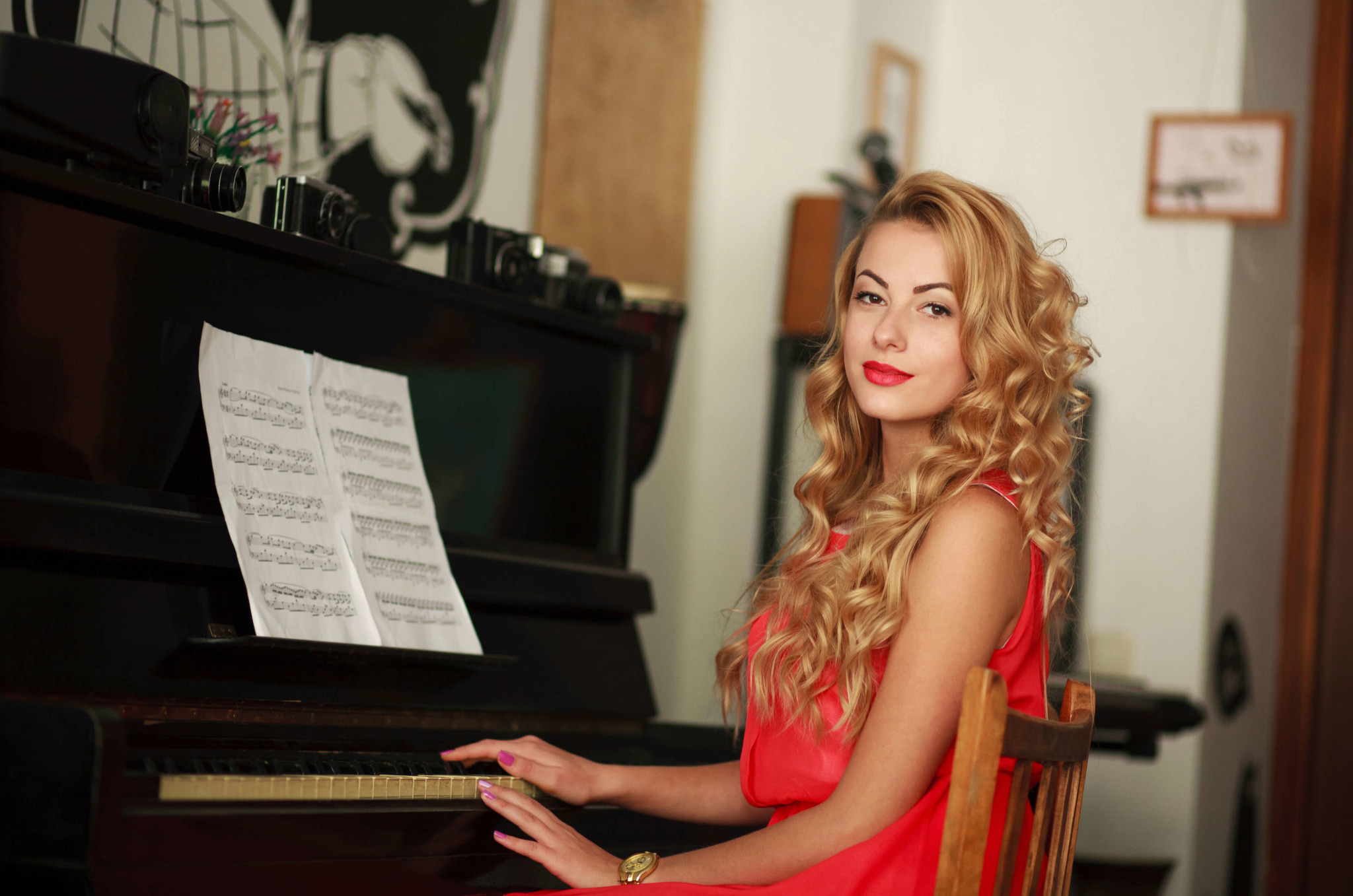 Beautiful young woman sitting at the piano in the room, practice